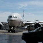 A Boeing 777-200 taxis toward the hangar